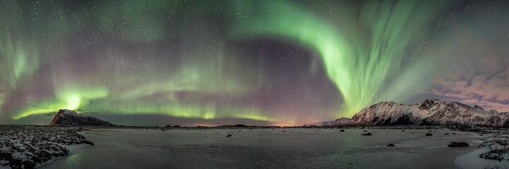 super wide panorama from arctic norway, frozen lake and aurora borealis dancing in the sky, winter landscape and illuminated mountaisn