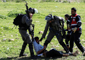 Israeli border policemen detain a wounded Palestinian, during clashes near the Jewish settlement of Beit El, near Ramallah, in the occupied West Bank