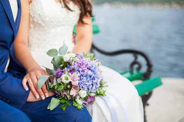 Bride and groom hold wedding bouquet from blue hydrangea, pink, lilac flowers outdoor. Couple sit on bench by sea after ceremony. Newlyweds are just married. Women is dressed in gown, man is in suit.