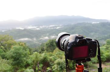 DSLR Camera set on camera tripod for take a landscape photo in selective focus.