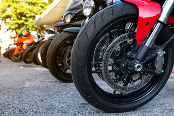 Motorcycle front wheel with red mud guard and twin disc brake.