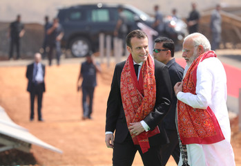 Indian Prime Minister Narendra Modi and French President Emmanuel Macron talk during the inauguration of a solar power plant in Mirzapur