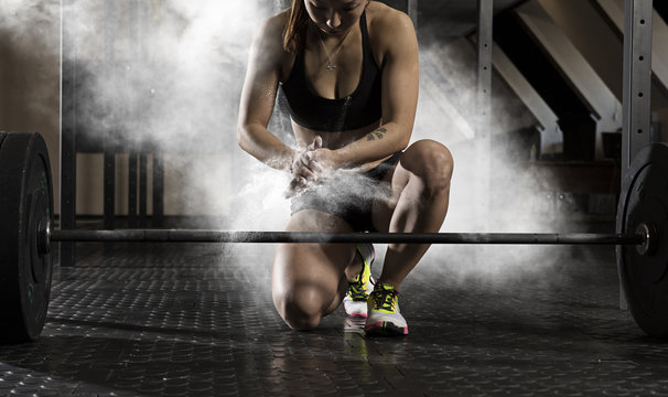 Woman workout with barbell at gym