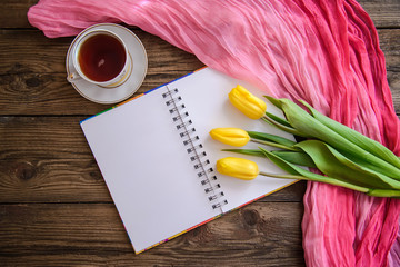 Romantic picture with notepad, tulips and a cup of tea on wooden background