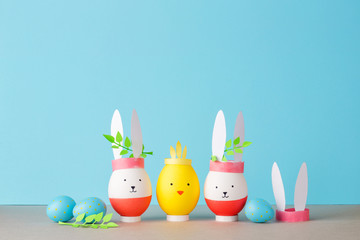 Easter holiday concept with cute handmade eggs: animals bunnies, chicken and quail egg. young branches green behind the ears. blue background and copy space
