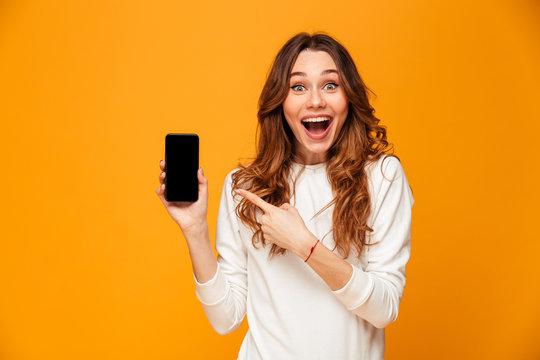 Surprised happy brunette woman in sweater showing blank smartphone screen