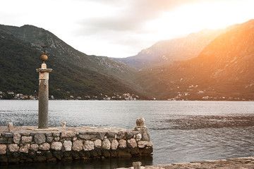 Monument on Island on the lake in Montenegro. Sun flare