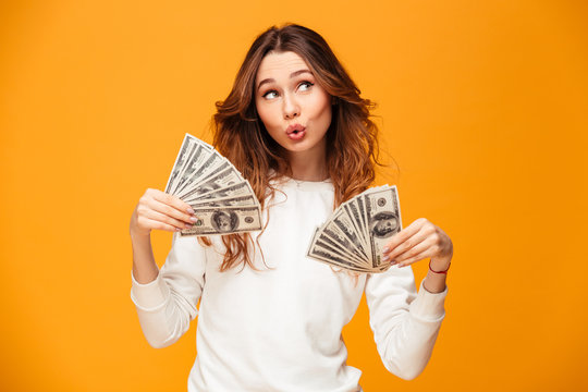 Pleased brunette woman in sweater holding money and waving them