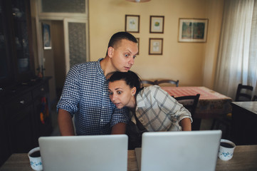 Young couple sitting in front of computers