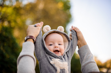 Father hands raising a cute smiling little son in the park