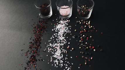 Glasses with flavored salt, assorted peppercorns and red spice on black background