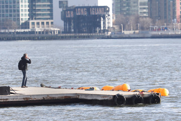 Yellow flotation devices mark the area where wreckage of a chartered Liberty Helicopters helicopter, that crashed into the East River is submerged, in New York