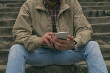 Modern attractive man texting on cellphone while sitting on the stairs.