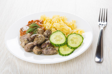 Plate with fried chicken hearts, pasta, baked eggplants, cucumbers, fork