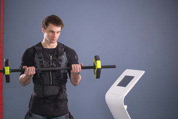 Man wearing electrostimulation suit working out EMS training with barbell closeup, power pose