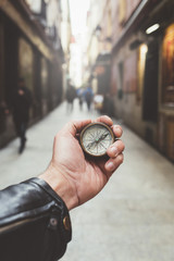 Hand of person holding compass in Madrid city