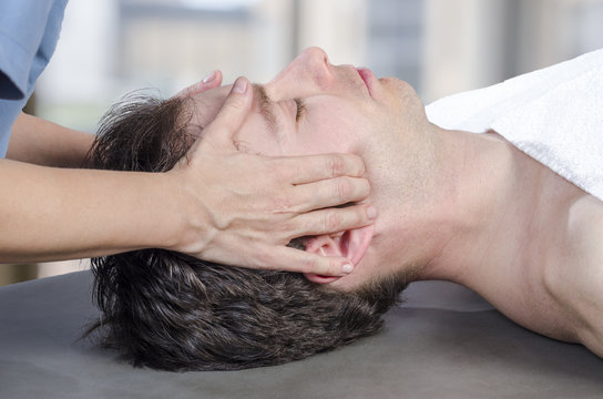 Physiotherapist, chiropractor assessing the muscles on a jaw. Osteopathy.