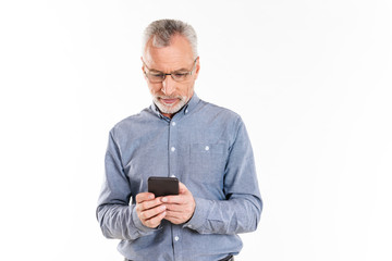 Mature concentrated man using smartphone isolated