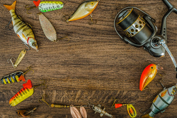Fishing gear on a wooden surface background.