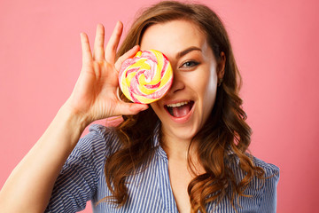 Portrait of a happy pretty girl holding sweet candy over pink background