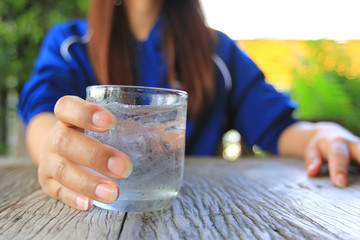 Closeup of young woman hand holding glass of water on table in restaurant