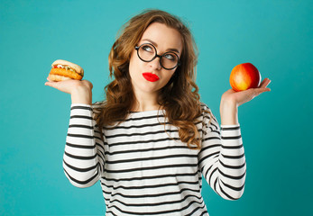 Portrait of young beautiful blond woman wearing glasses  holding red apple in one hand and burger in another over blue background