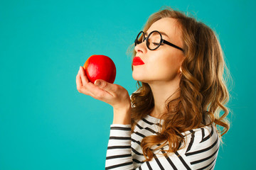 Portrait of young beautiful woman in round black glasses eating red apple over blue background