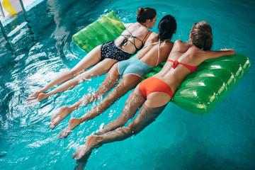 Close-up back view of female legs. Three fit women in swimwear swimming in blue sea water using air mattress