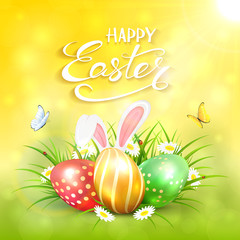 Yellow sunny background with Easter eggs and rabbit ears in grass