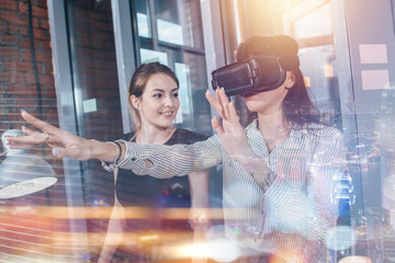 Female office workers having fun at work watching 3d video in VR goggles, woman touching something experiencing virtual reality