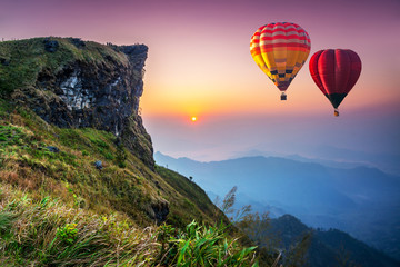 Colorful hot air balloons flying over mountain at Phu Chi fa National Park in the morning. Chiang Rai Province, Thailand