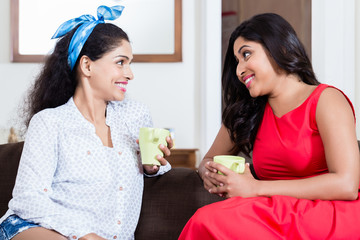 Two young female friends smiling while drinking tea or coffee indoors at home