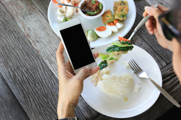 Businessman holding smartphone and having lunch in restaurant