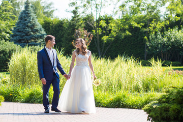bride and groom smiling each other walking in the park for hands