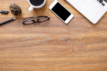 Wood office desk table with laptop computer, smartphone, cup of coffee and office supplies. Top view with copy space, flat lay.