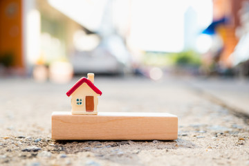 Miniature colorful house on wooden block using as property and financial concept