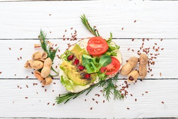 Burger, avocado sandwich, cherry tomatoes and lettuce leaves. On a wooden background. Top view. Copy space.