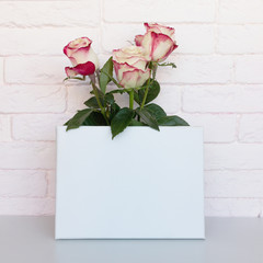 Mockup poster frame with flowers. White blank canvas. Pink brick wall on background.