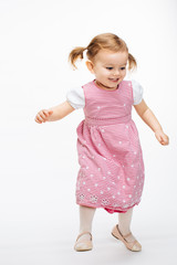 Full body portrait of a happy energetic toddler girl captured in movement, dancing girl with ponytails