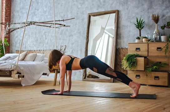 Young woman practicing yoga, stretching in Utthita parsvakonasana