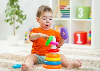 Baby toddler makes funny faces playing with educational toy on floor