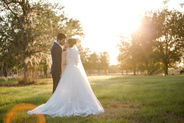 Hispanic Bride and Groom Portrait on Wedding Day Kissing in a Field