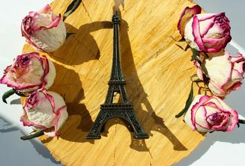 Eiffel tower sovenir among flowers on wooden background