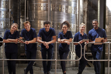 A row of staff at a wine factory smiling to camera, close up