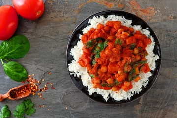 Spicy tomato curry chickpea rice dish. Top view, flat lay over a dark stone background.
