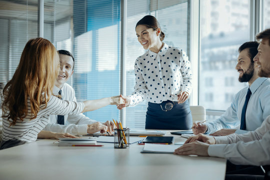 Pleasant cooperation. Upbeat young female boss shaking hands with her female colleague, congratulating her with promotion, while carrying out a meeting