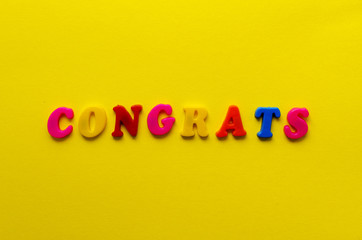 word 'congrats' from magnetic letters on yellow paper background