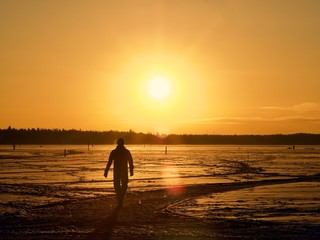 A man walking toward the sunset on the frozen sea, Espoo, Finland