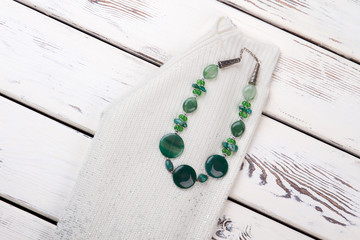 Necklace with green polished stones. Cropped photo of white woolen sweater with accessorie.