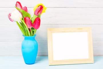 Colorful red spring tulip flowers in nice blue vase and blank photo frame on light wooden background as greeting card. Mothersday or spring concept